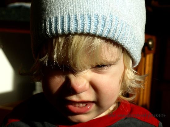 Blond toddler boy blue hat moster face