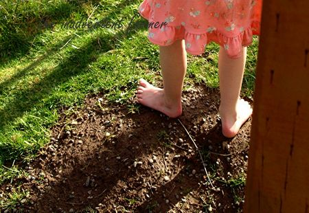 Little girl bare feet in garden