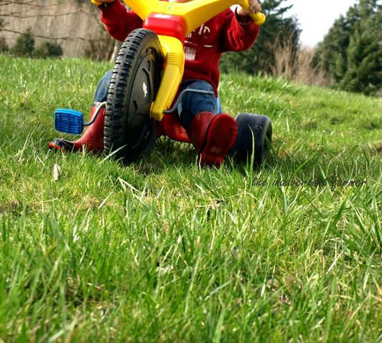 Big wheel boy grass red boots
