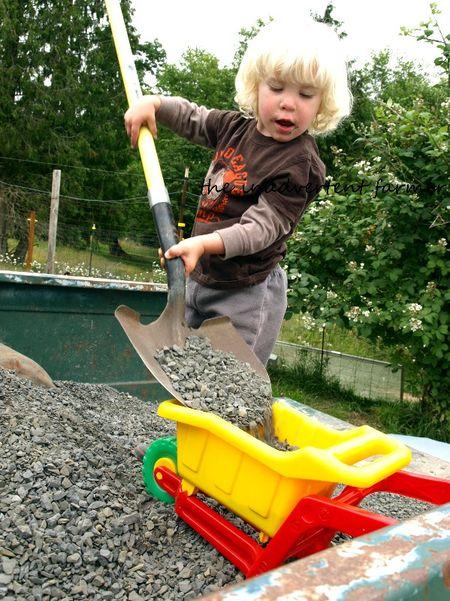 Hauling gravel little boy wheelbarrow