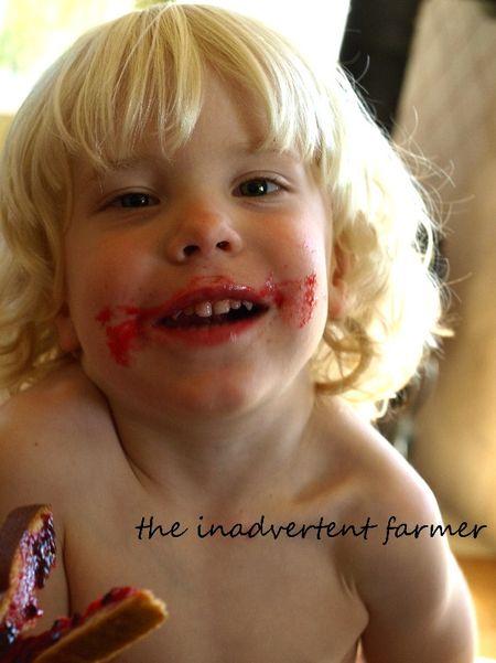 Plum berry jam on little boy face