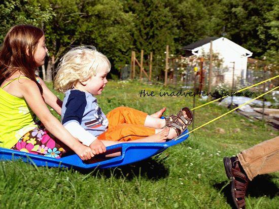 Grass sledding catching air boy girl