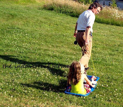 Grass sledding dad pull kids
