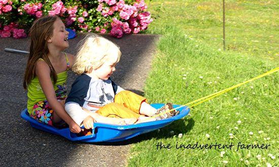 Grass sledding boy girl