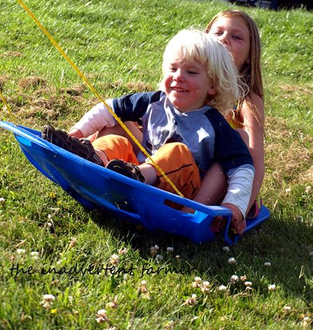 Grass sledding fun boy girl