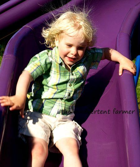 Playground slide blond boy static