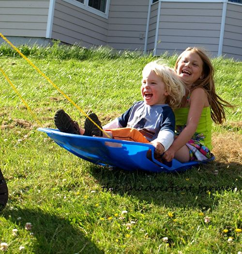Grass sledding boy girl summer