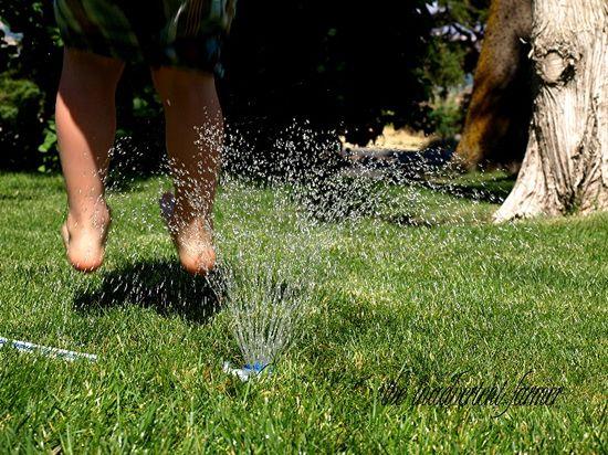Sprinkler feet jump summer boy